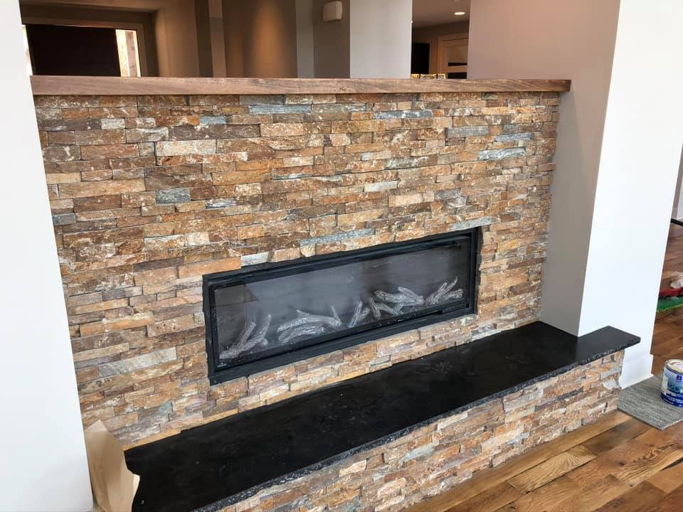 Stone fireplace with granite hearth in local KC metro residence.